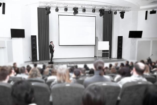 기자 회견 동안 무대에 서있는 사업가 남자. 비즈니스 개념