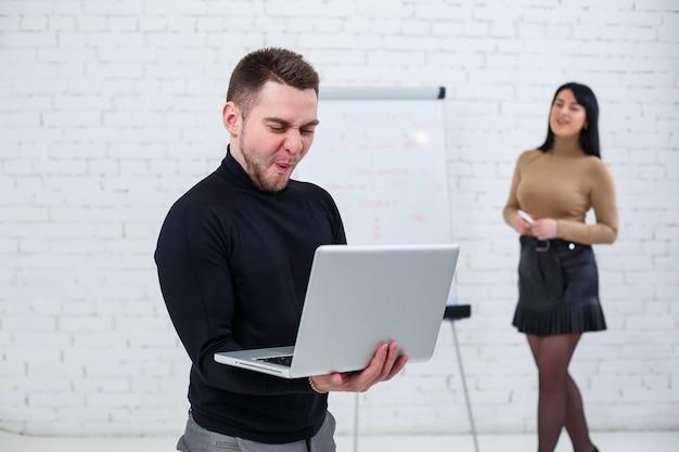 Бизнесмен мужчина стоит с ноутбуком, пока женщина пишет бизнес-план на белой доске. встаньте на белом фоне. девушка изучает новые бизнес-правила со студенткой