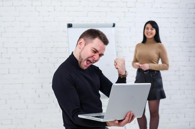 Бизнесмен мужчина стоит с ноутбуком, пока женщина пишет бизнес-план на белой доске. встаньте на белом фоне. девушка изучает новые бизнес-правила со студенткой Premium Фотографии