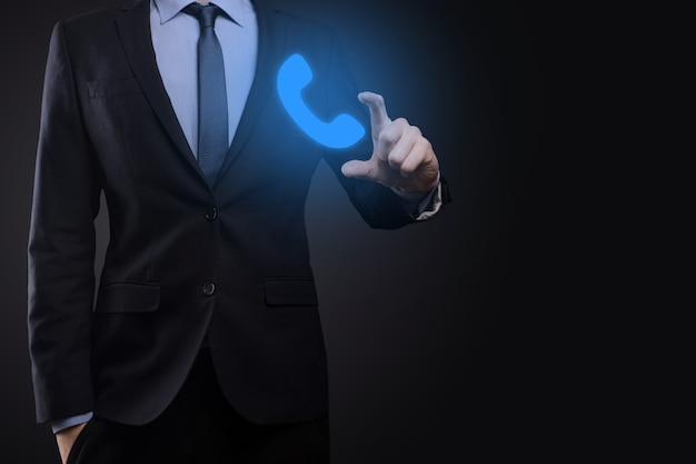Businessman man in suit on black background hold phone icon.call now business communication support center customer service technology concept.