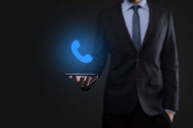 Businessman man in suit on black wall hold phone icon.call now business communication support center customer service technology concept.