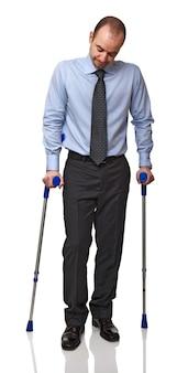 Бизнесмен человек идет с костылем, изолированные на белом фоне