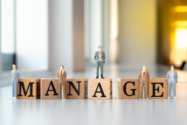 Businessman on manage text wooden blocks.