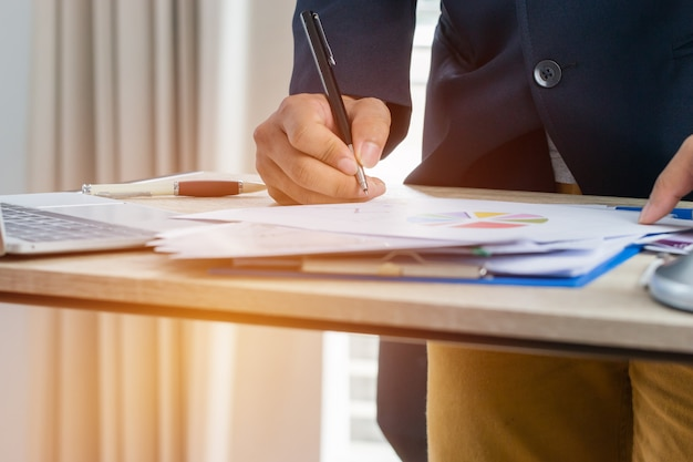 Businessman manager checking and signing documents reports papers