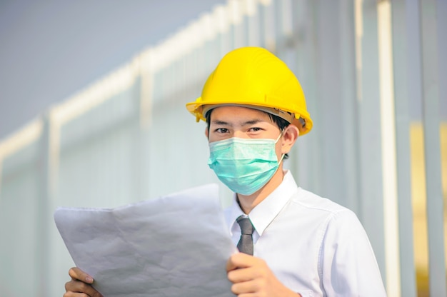 Businessman manager use face mask yellow hard hat holding blueprint work building construction