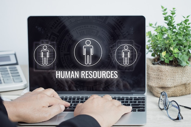 Businessman manager using computer with sign human-resources department (hr department) icons on laptop. business as compliance with labor law,employment standards, administration of employee benefits