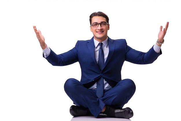 Businessman meditating on the floor isolated