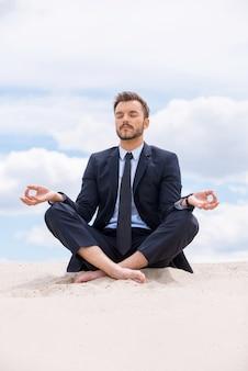 Бизнесмен медитирует. красивый молодой бизнесмен медитирует, сидя в позе лотоса на песке и против голубого неба