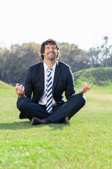 Businessman meditating in lotus position outdoors