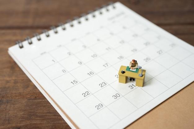 Businessman miniature on calendar
