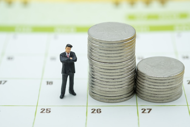 Businessman miniature figure people standing with stack of coins on calendar
