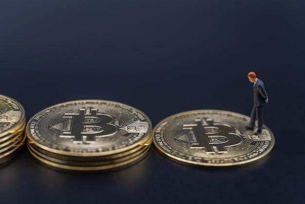 Бизнесмен миниатюрная фигура людей, идущих по стопке золотых биткойн-монет