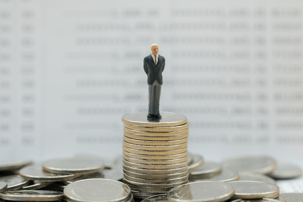 Businessman miniature figure stand on stack of coins with bank passbook