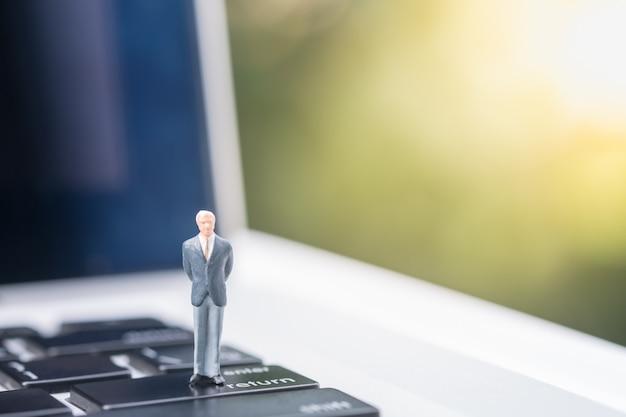 Businessman miniature figure standing on enter button