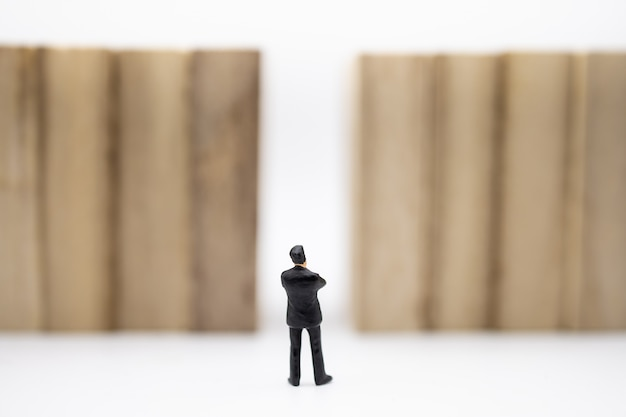 Businessman miniature figure standing in front of wooden block wall on white.