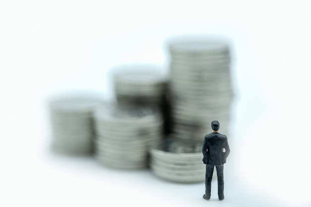 Businessman miniature figure standing and looking to stack of coins.