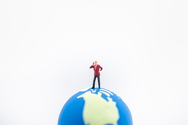 Businessman miniature figure standing and make call with mobile phone on mini world ball
