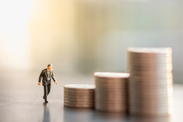 Businessman miniature figure walking to stack of coins.