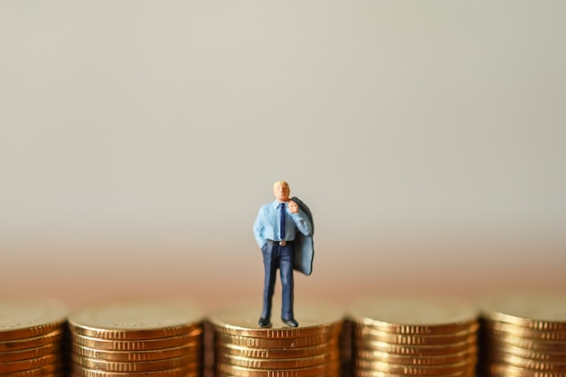 Businessman miniature figures people standing on top of stack of gold coin wiht copy space