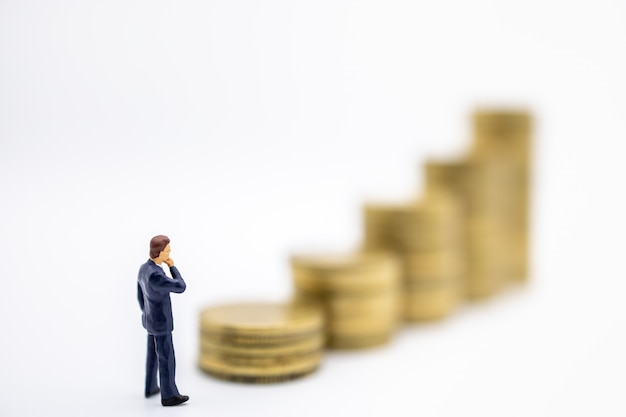 Businessman miniature figures standing and looking tp stack of gold coins on white.