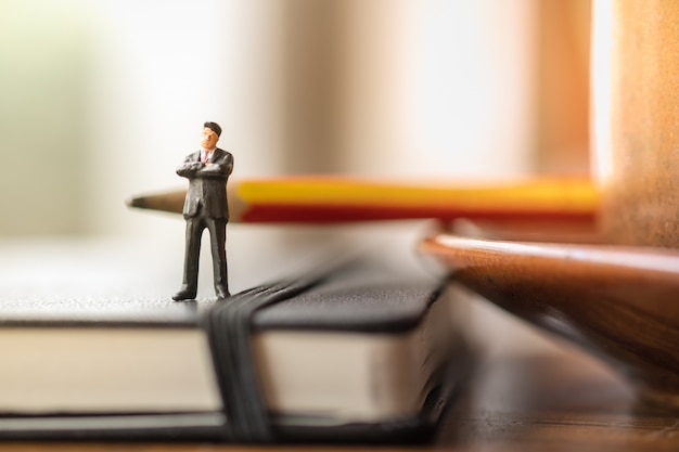 Businessman miniature figures standing on notebook with pencil with cup of coffee.