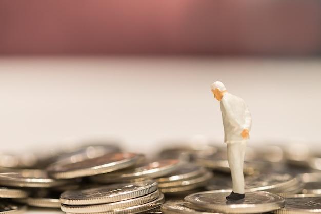 사업가 미니어처 사람들이 동전 더미에 서있는 그림