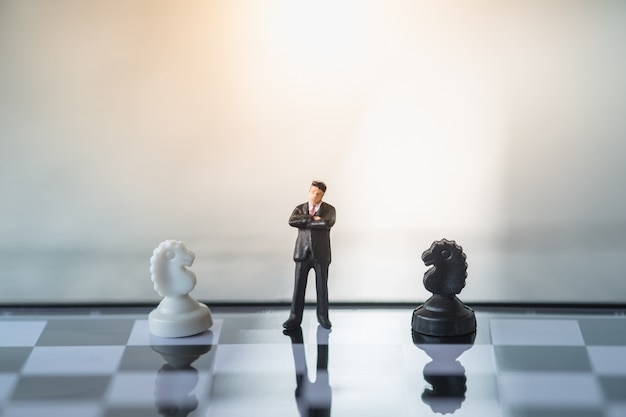 Businessman miniature standing on chessboard with black and white knight chess