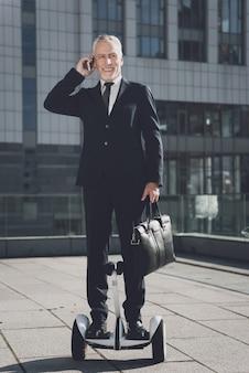 Businessman on mono-wheel speaks on the phone