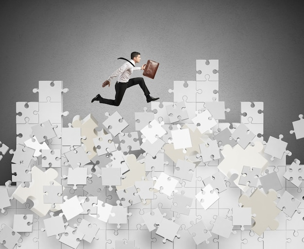 Businessman over a mountain by puzzle falling