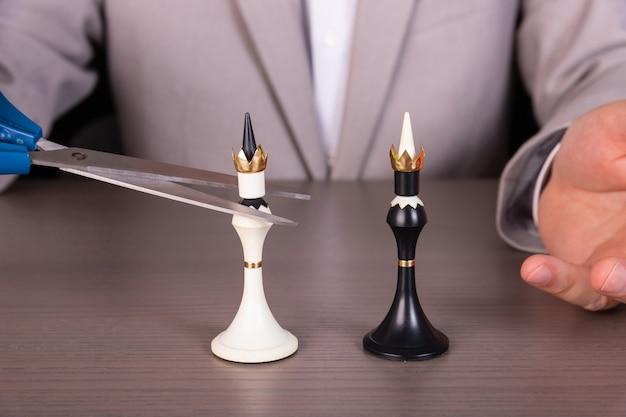 ビジネスマンはチェスの駒を移動し、ゲームに勝つために戦略的に考える