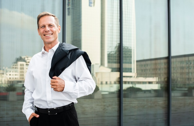 Businessman near glass building looking at camera