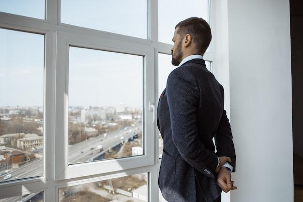 Businessman near window in office.