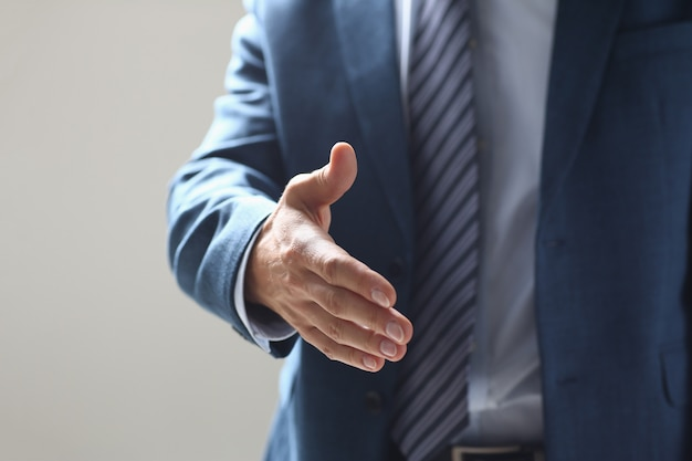 Businessman offer hand to shake as hello in office closeup