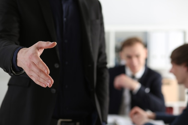 ビジネスマンは、オフィスのクローズアップでこんにちはとして振る手を提供します。