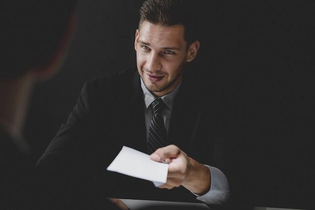Businessman offering bribe money in the envelope to partner