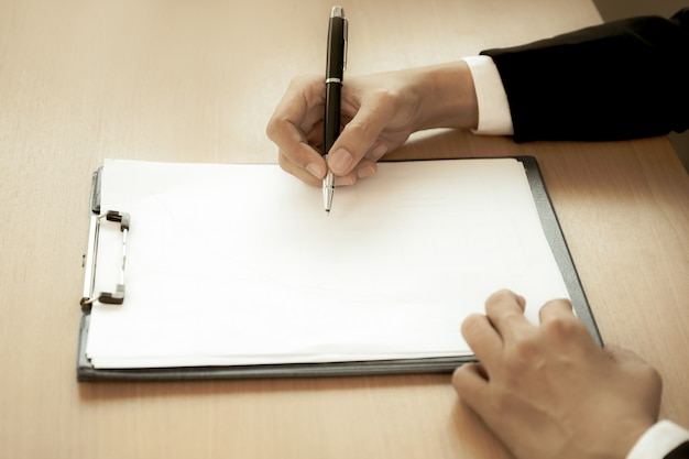 Businessman at office desk signing a contract form in creative aged photo.