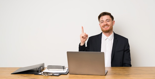 Businessman in a office showing and lifting a finger in sign of the best