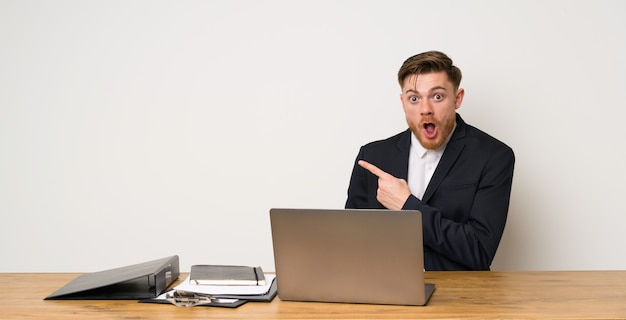 Businessman in a office surprised and pointing side