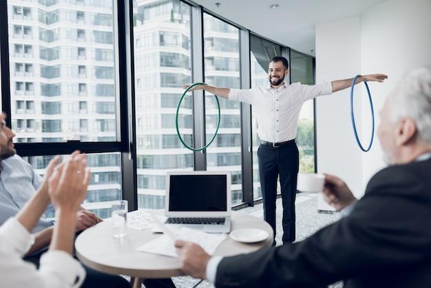 Businessman in the office turns hula-hoop.
