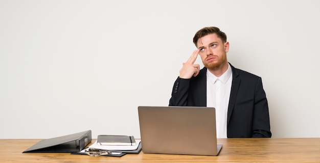 Businessman in a office with problems making suicide gesture