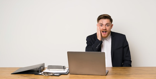Businessman in a office with surprise and shocked facial expression