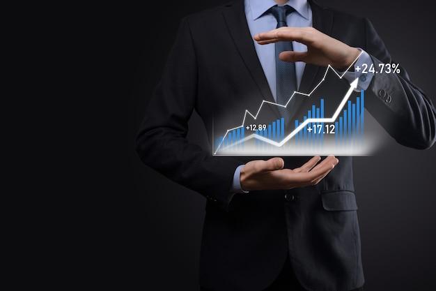 Бизнесмен на черном фоне нажимает, нажимает пальцем на стрелку положительного роста. графики индикаторов. концепция развития бизнеса и финансов.