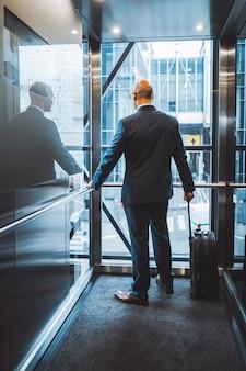 出張中のビジネスマンがホテルに到着し、スーツケースをハンドルに持ってカメラに背を向けて立っているエレベーターに立ち上がる。
