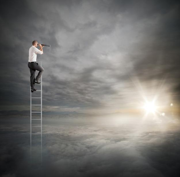 Бизнесмен на лестнице высоко в небо смотрит в бинокль