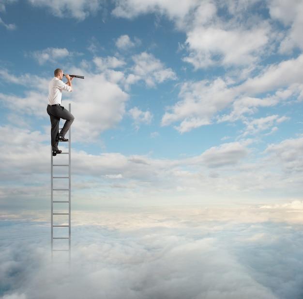 双眼鏡で見ている空高くはしごのビジネスマン