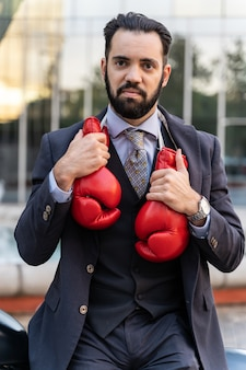Бизнесмен на мотоцикле в красных боксерских перчатках, свисающих с шеи