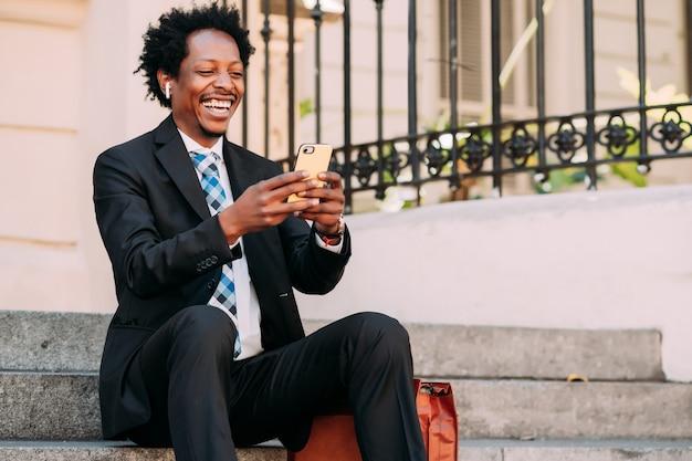 屋外の階段に座っている間彼の携帯電話でビデオ通話中のビジネスマン。ビジネスと技術の概念。