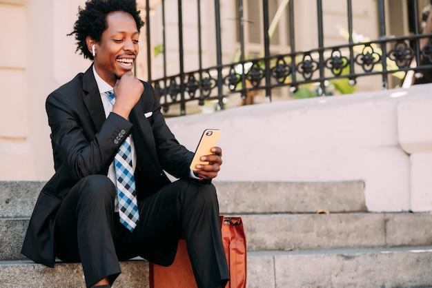 屋外の階段に座っている間彼の携帯電話でビデオ通話中のビジネスマン。