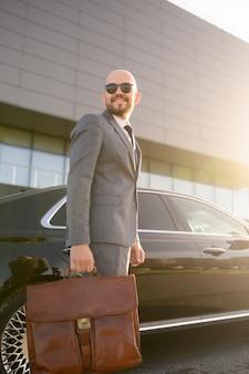 晴れた日に高価な車の背景に実業家