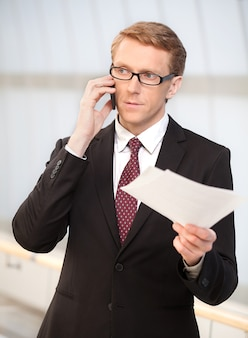 이동 중에 사업가입니다. 휴대 전화로 이야기하고 문서를 손에 들고 있는 정장 차림의 자신감 있는 노인